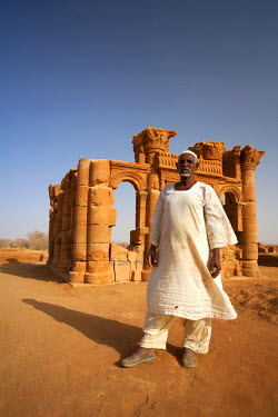 SUD1166 Sudan, Nagaa. The solitary guide at the remote ruins of Nagaa stands in front of the ruins.