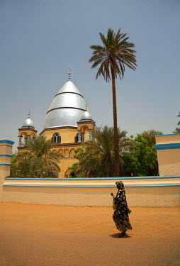 SUD1173 Sudan, Khartoum. A woman walks past the Mahdi's Tomb on a hot Khartoum day.