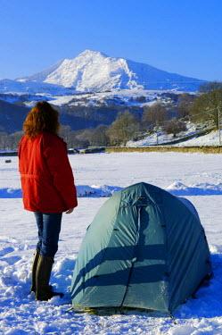WAL7021 Wales, Gwynedd, Snowdonia. A camper by her tent looking towards Moel Siabod. (MR)