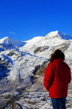 WAL7026 Wales, Gwynedd, Snowdonia. A walker looks westwards to the snow covered slopes of Snowdon. (MR)
