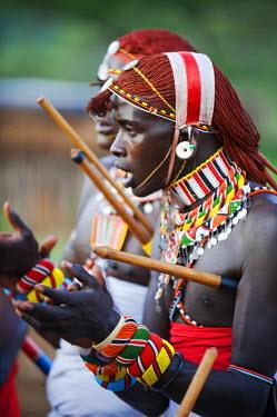 KEN6665 Kenya, Laikipia, Ol Malo.  Samburu warriors sing, clap and dance in their traditional dress at a manyatta