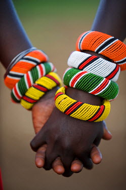 KEN6666 Kenya, Laikipia, Ol Malo.  A Samburu boy and girl hold hands at a dance in their local manyatta.