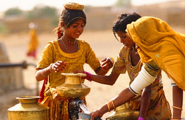 IND5883 Tribal women and girls collecting water from a well in the desert near Jaisalmer, State of Rajasthan, India