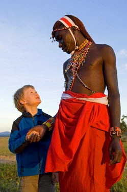 KEN6775 Kenya, Laikipia, Lewa Downs.  A young boy on a family safari with one of the Laikipiak Maasai guides. (MR)