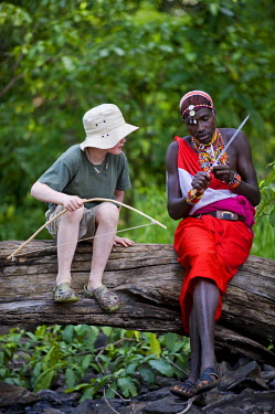KEN6816 Kenya, Laikipia, Lewa Downs. One Wilderness Trails' Laikipiak Maasai guides shows child how to sharpen an arrow.