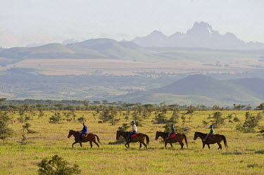 KEN6827 Kenya, Laikipia, Lewa Downs.  A family on a horse riding safari with Mount Kenya in the background.