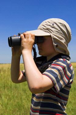 KEN7123 Kenya, Masai Mara.  A young boy on safari looks out across the savannah with his binoculars (MR)
