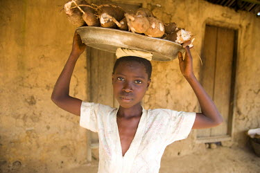 AF19_PBO0069 Young woman carrying large plate of cassava on her head, Dakoto Junction, Ghana