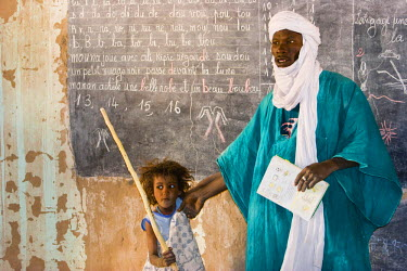 AF26_PLA1039 Mali. Tuareg teacher and girl in front of a blackboard at a primary school