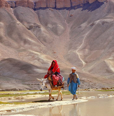 AS01_RER0052 Afghanistan, Band-i-Amir. A couple, the woman on a donkey, travel along the road near Band-i-Amir in