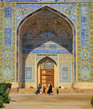 AS01_RER0064 Afghanistan, Herat. Visitors walks past ornate tiled walls at the colorful Friday Mosque, or Masjid-i-Jami, in Herat