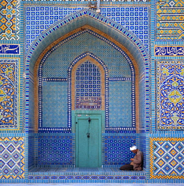 AS01_RER0091 Afghanistan, Mazar-i-Sharif. A man sits reading in the colorful archway at the Shrine to Hazrat Ali in Mazar-i-Sharif,