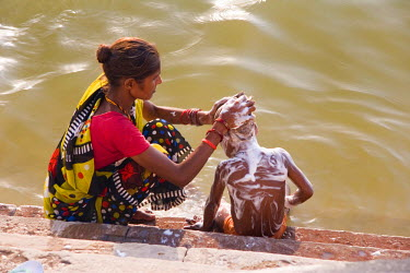 AS10_MWR0034 Varanasi, India. A mother bathing her son in the Ganges river.