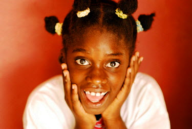 AF02_AAS0000 Angola, Portrait of an eight-year-old African girl with braids and a white shirt standing in front of a pink wall, her hands supporting her head, looking happily surprised