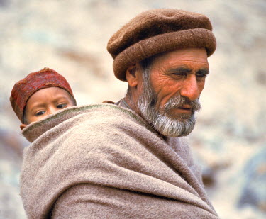 AS28_RER0015 Pakistan, N-W Frontier Province, Gilgit. A father carries his son on his back in Chitral, North-West Frontier Province, Pakistan.