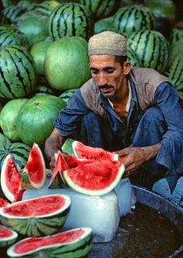 AS28_RER0039 Pakistan, N-W Frontier Province, Peshawar. A melon vendor slices watermelon in the bazaar in Peshawar, North-West Frontier Province, Pakistan.