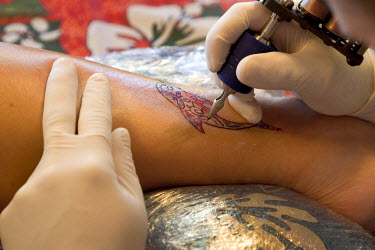 OC13_BJA0182 French Polynesia, Society Islands, Moorea. Tattoo being drawn on woman's ankle