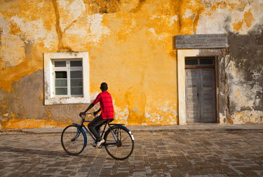 MOZ1444 Mozambique, Ihla de Mo�ambique, Stone Town. A boy cycles through the cobbled streets of Stone Town.
