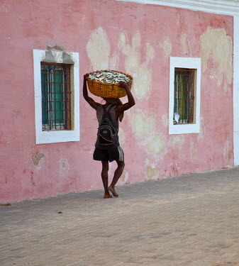 MOZ1458 Mozambique, Ihla de Mo�ambique, Stone Town. A man walks with his catch through the brightly-painted buildings