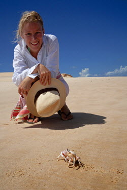 MOZ1479 Mozambique,  Bazaruto Archipelago. A tourist gets close to an inquisitive Ghost Crab. MR