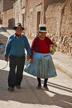 PER33426 Peru, A happy couple walking down the main street of Maras, situated on a high plateau almost 11,000 ft above sea level.