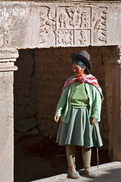 PER33427 Peru, An Indian woman stands at the entrance to her house with a Spanish nobility coat of arms, an indication of the past.