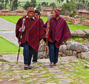 Peru, Elected community representatives, staffs of office in hand, stride along cobblestone paths at Chinchero