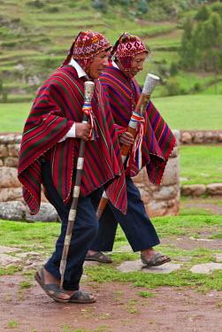 PER33438 Peru, Elected community representatives, staffs of office in hand, stride along cobblestone paths at Chinchero