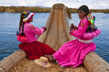 PER33515 Peru, two girls from Uros row a reed boat to one of the unique floating islands of Lake Titicaca.