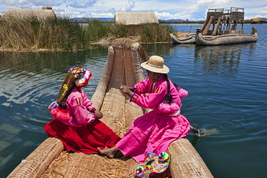 PER33516 Peru, Two girl from Uros row a reed boat to one of the unique floating islands of Lake Titicaca.