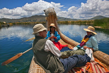 PER33517 Peru, Tourists being rowed in a traditional reed boat around the unique floating islands of Uros on Lake Titicaca.