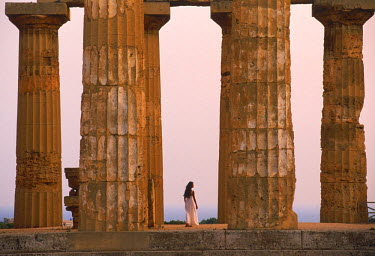 NP00866521 Woman walking through ruins of Greek temple from 7th Century BC at Selinunte in Trapani Province on Sicily