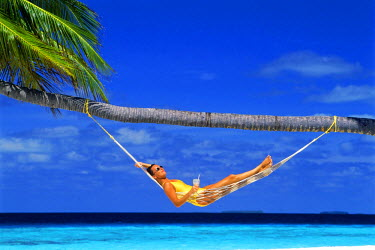 NP01578259 Woman relaxing in hammock under palm tree with tropical drink