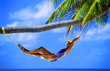 NP01578261 Woman with sunglasses relaxing in hammock under palm tree in Maldive Islands