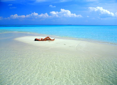 NP01855975 Woman alone on sandbar in Maldive Islands surrounded by Indian Ocean