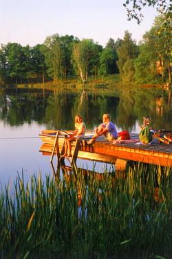 NP00865648 Two girls 11 to 13 enjoying fishing picnic on lakeside pier in Sweden at sunset