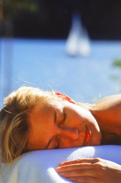 NP01855889 Sweden, Woman resting on table outdoors in summer sun after massage