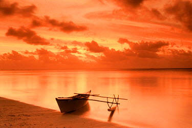 NP01114633 Outrigger canoe on shore in Aitutaki lagoon at sunset, Cook Islands