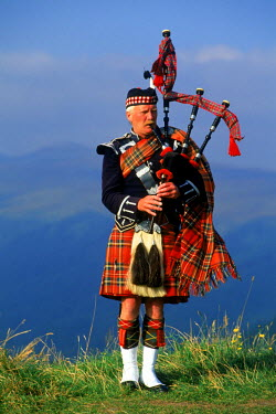 NP01114621 Bagpiper at Loch Broom in Scottish highlands