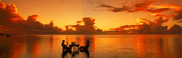 NP01114761 Couple sitting at table sharing sunset drink in Aitutaki lagoon, Cook Islands
