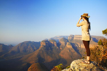 SAF6030AW Woman looking through binoculars at Three Rondavels, Blyde River Canyon, Drakensberg Escarpment, Mpumalanga, South Africa (MR)