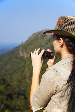 SAF6027AW Woman with binoculars on top of canyon, Graskop, Drakensberg Escarpment, Mpumalanga, South Africa (MR)