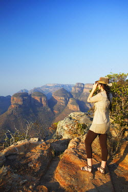 SAF6110AW Woman looking through binoculars at Three Rondavels, Blyde River Canyon, Drakensberg Escarpment, Mpumalanga, South Africa (MR)