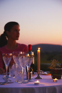 SAF6122AW Woman sitting at table for dinner at River Bend Lodge, Addo Elephant Park, Eastern Cape, South Africa (MR)