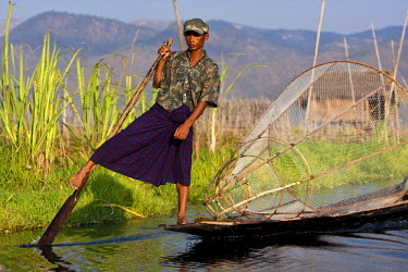 Myanmar, Inle Lake. Intha fisherman with traditional conical fish net, gently paddling his flat-bottomed boat home.