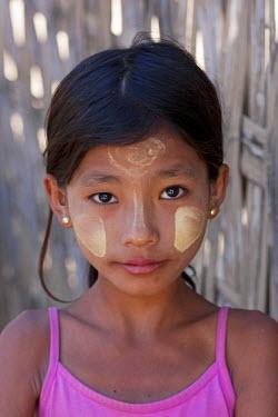MYA1451 Myanmar, Burma, Mrauk U. Young village girl with her face decorated with thanaka, a local sun cream made from ground bark, Mrauk U, Rakhine State.