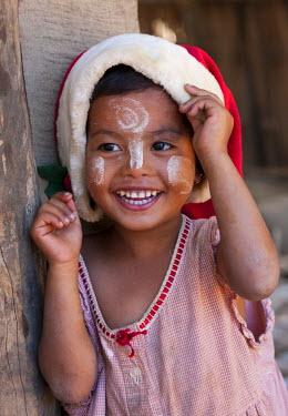 MYA1452 Myanmar, Burma, Mrauk U. Young village girl wearing a Christmas hat, her face decorated with thanaka, a local sun cream made from ground bark, Mrauk U, Rakhine State.
