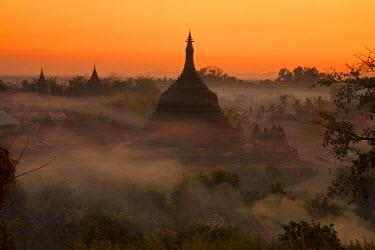 MYA1454 Myanmar, Burma, Mrauk U. Evening mist and smoke from village cooking fires swirl around Ratanabon Paya, Mrauk U, Rakhine State.