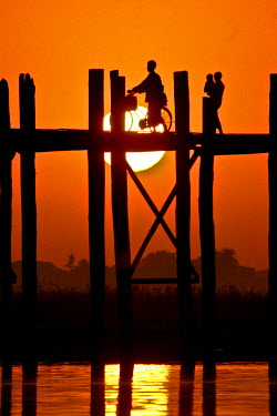 MYA1462 Myanmar, Burma, Amarapura, Taungthaman Lake, U Bein's Bridge.  A family walking home at sunset over U Bein's Bridge, over 200 years old and the world's longest teak span.