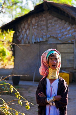 MYA1491 Myanmar, Burma, Loikaw. A Padaung (long-neck) woman standing outside her house, wearing her traditional brass neck coils, the weight of which pushes her collarbone down. Loikaw.